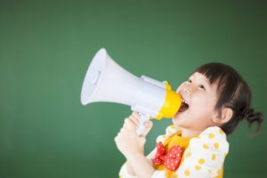 cute child using a megaphone in a classroom at school